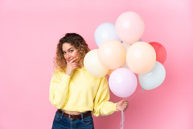 Молодая блондинка с вьющимися волосами ловит много воздушных шаров, изолированных на розовом, думая об идее