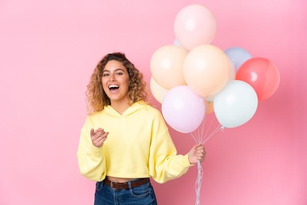 Молодая блондинка с вьющимися волосами ловит много воздушных шаров, изолированных на розовой стене, указывает пальцем на вас