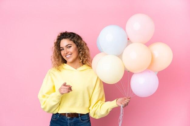 분홍색 벽에 고립 된 많은 풍선을 잡는 곱슬 머리를 가진 젊은 금발의 여자는 당신에 손가락을 가리 킵니다