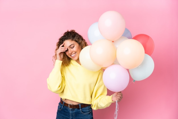 Young blonde woman with curly hair catching many balloons isolated on pink wall laughing