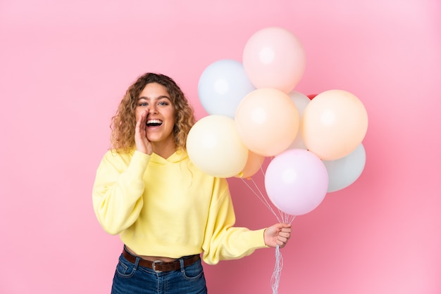 Young blonde woman with curly hair catching many balloons isolated on pink wall shouting with mouth wide open