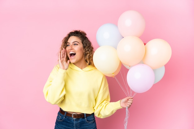 Young blonde woman with curly hair catching many balloons on pink wall shouting with mouth wide open