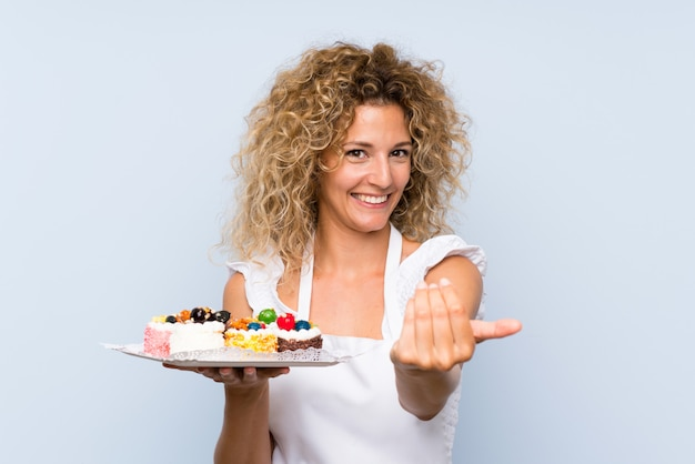 Young blonde woman with curly hair holding lots of different mini cakes inviting to come with hand. happy that you came