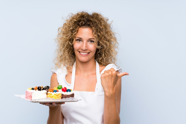 Young blonde woman with curly hair holding lots of different mini cakes pointing to the side to present a product