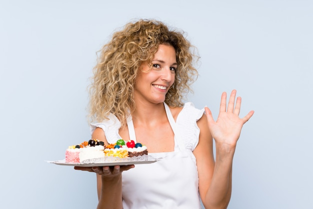 Young blonde woman with curly hair holding lots of different mini cakes saluting with hand with happy expression