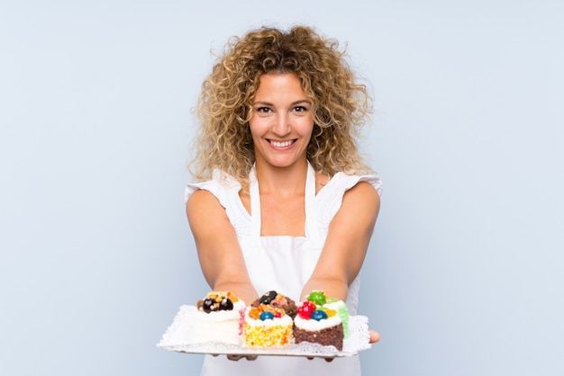 Young blonde woman with curly hair holding lots of different mini cakes