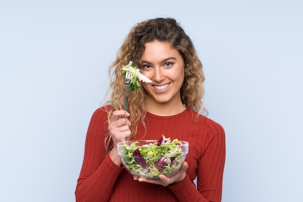 Young blonde woman with curly hair holding a salad over isolated wall