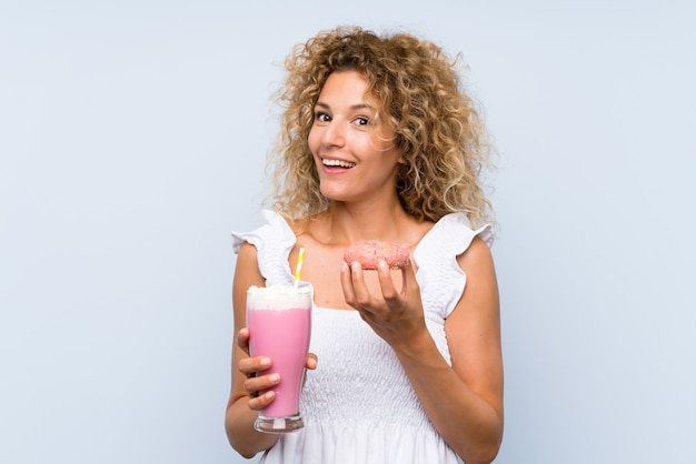 Young blonde woman with curly hair holding a strawberry milkshake and a donut
