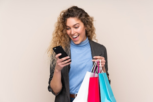 Young blonde woman with curly hair isolated on beige holding shopping bags and writing a message with her cell phone to a friend
