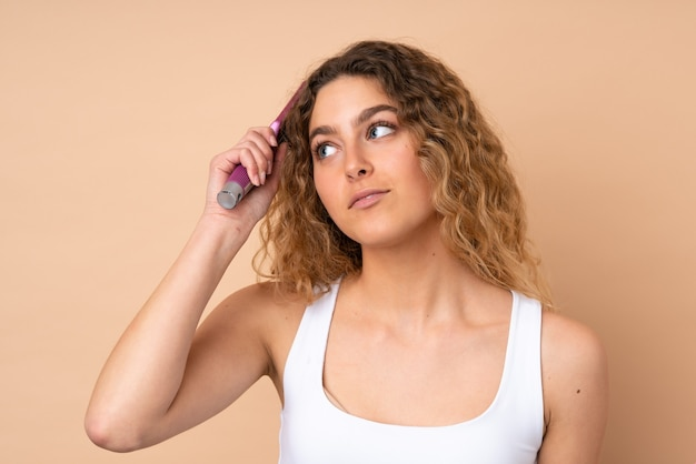 Young blonde woman with curly hair isolated on beige with hair comb