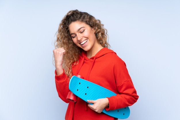 Young blonde woman with curly hair isolated on blue wall with a skate