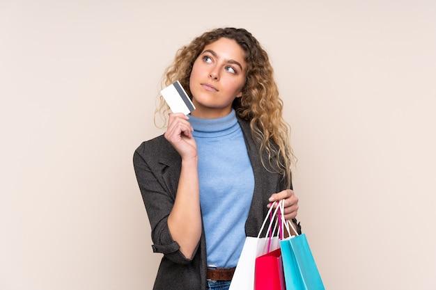 ショッピングバッグとクレジットカードを保持し、考えているベージュの背景に分離された巻き毛の若いブロンドの女性