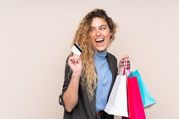 ショッピングバッグとクレジットカードを保持しているベージュに分離された巻き毛の若いブロンドの女性