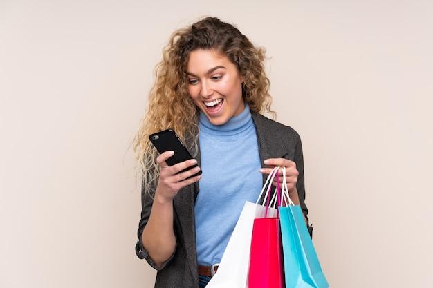 Молодая блондинка с вьющимися волосами изолирована на бежевом, держит сумки для покупок и пишет сообщение по мобильному телефону другу