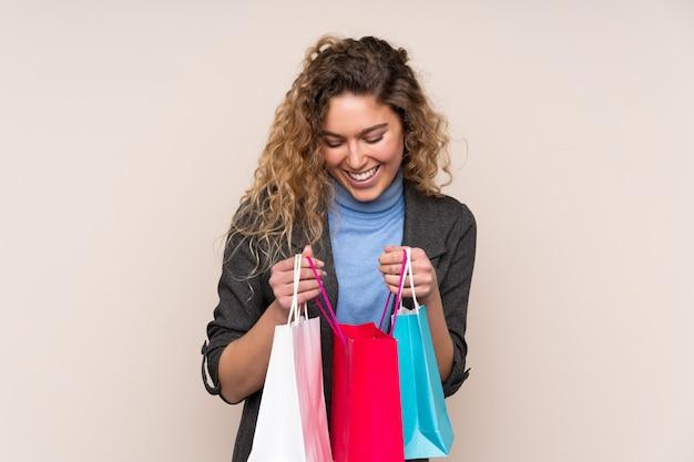 쇼핑 가방을 들고 내부를 찾고 베이지 색 벽에 고립 곱슬 머리를 가진 젊은 금발의 여자