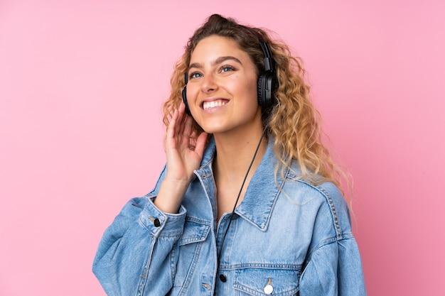Молодая блондинка с вьющимися волосами изолирована на розовой слушающей музыке