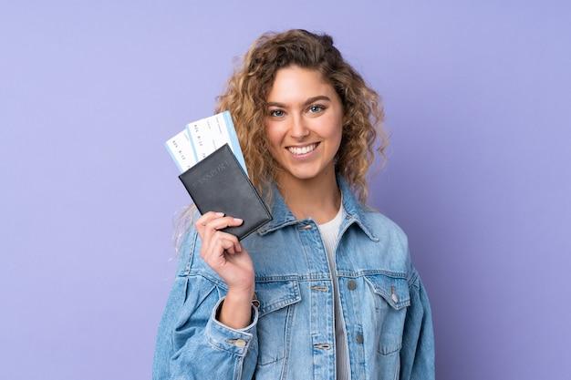 Молодая блондинка с вьющимися волосами, изолированными на фиолетовом, счастлива в отпуске с паспортом и билетами на самолет