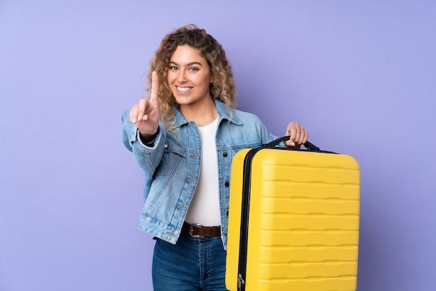 旅行スーツケースと1つを数えて休暇で紫に分離された巻き毛の若いブロンドの女性