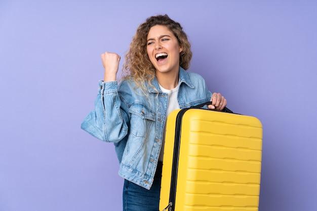旅行スーツケースと休暇で紫に分離された巻き毛の若いブロンドの女性
