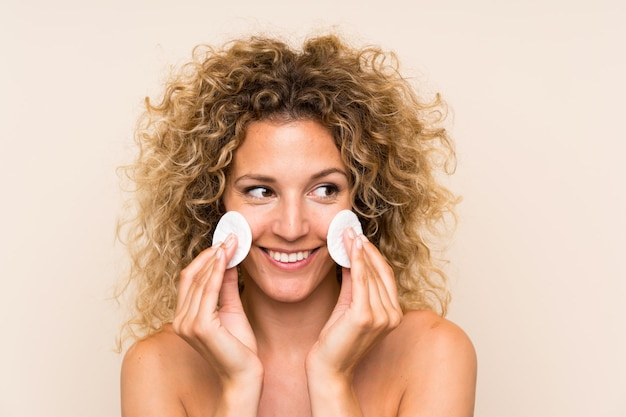 Young blonde woman with curly hair removing makeup from her face with cotton pad