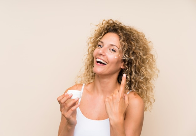 Young blonde woman with curly hair with moisturizer