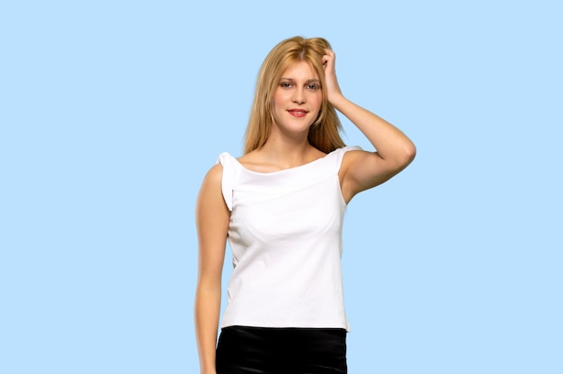 Young blonde woman with an expression of frustration and not understanding on isolated blue background
