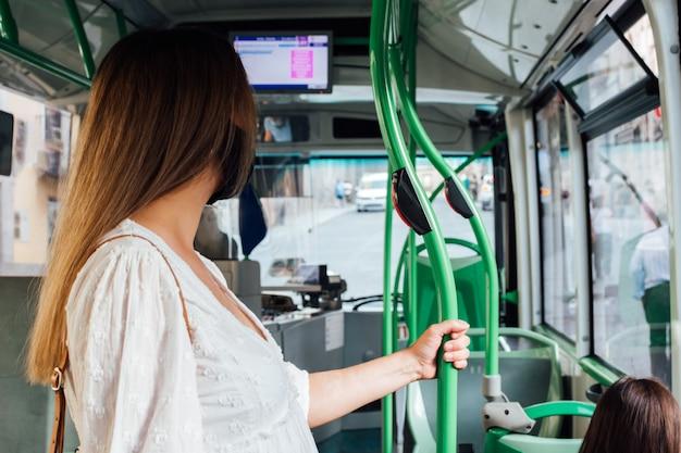 도시 버스 여행을 만드는 얼굴 마스크와 젊은 금발의 여자. 버스 정류장에서 내리기를 기다리고 있습니다.