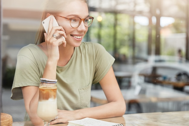 Young blonde woman with glasses in cafe