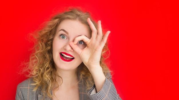 Молодая блондинка с зелеными глазами смотрит в камеру сквозь пальцы в жесте хорошо