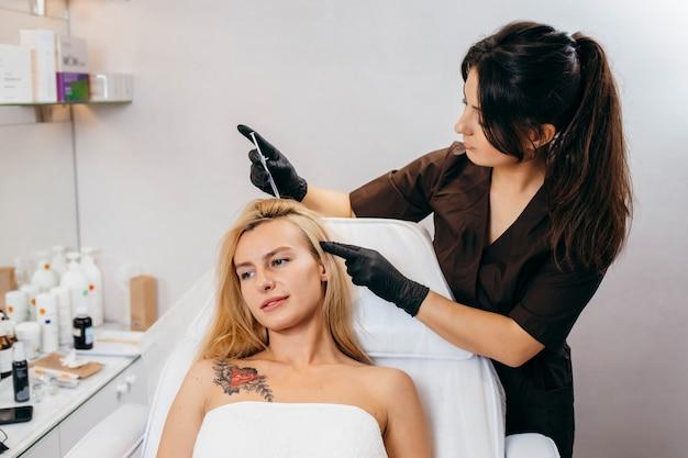 Молодая белокурая женщина с проблемой выпадения волос получая впрыску