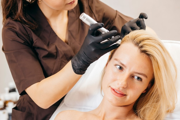 Young blonde woman with hair loss problem receiving injection
