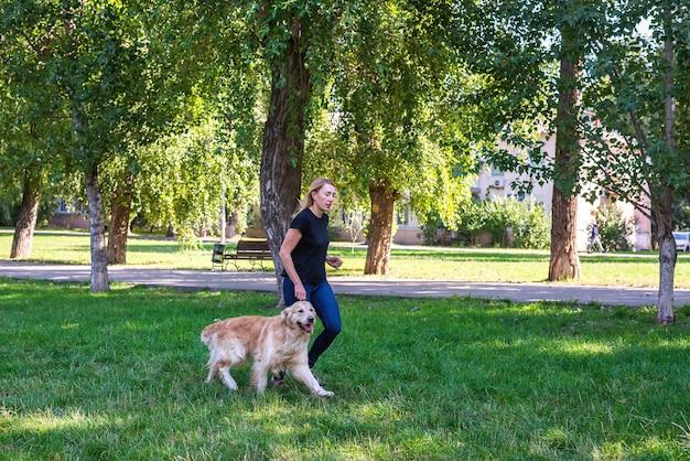 공원에서 그녀의 강아지 리트리버와 함께 젊은 금발의 여자