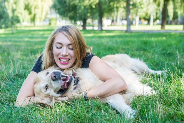 Young blonde woman with her dog retriever in the park