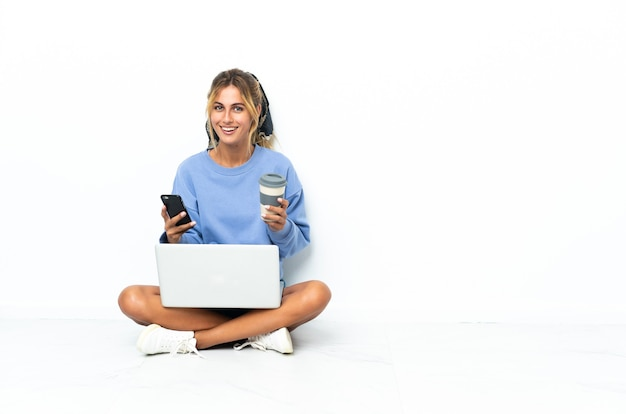 Young blonde woman with the laptop isolated holding coffee to take away and a mobile