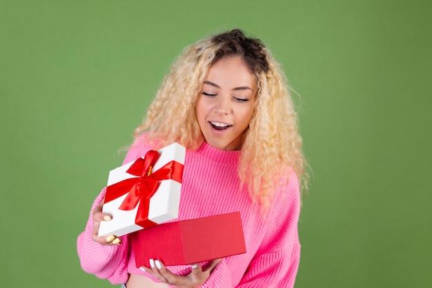 Молодая блондинка с длинными вьющимися волосами в розовом свитере на зеленом открывает подарок