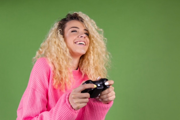 Young blonde woman with long curly hair in pink sweater on green with joystick playing games
