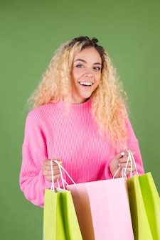Young blonde woman with long curly hair in pink sweater on green with shopping bags