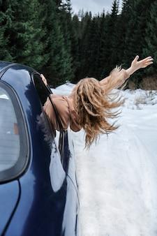 바람을 잡는 차에 긴 머리를 가진 젊은 금발의 여자