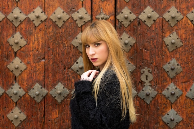 Young blonde woman with long hair posing on an antique wooden door.