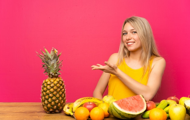 Young blonde woman with lots of fruits extending hands to the side for inviting to come