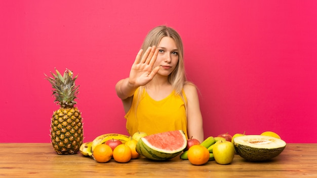 Young blonde woman with lots of fruits making stop gesture with her hand