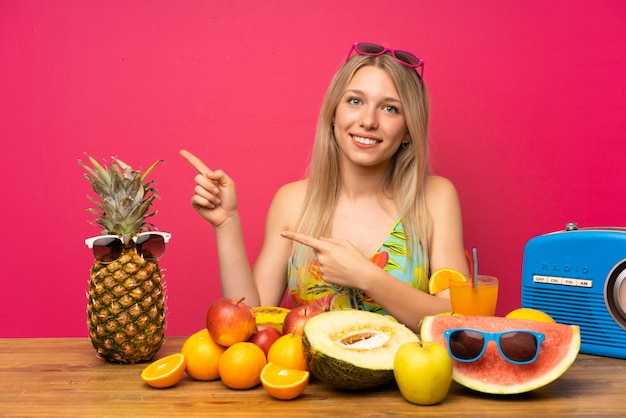 Young blonde woman with lots of fruits pointing finger to the side