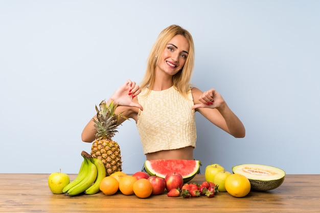 Young blonde woman with lots of fruits proud and self-satisfied