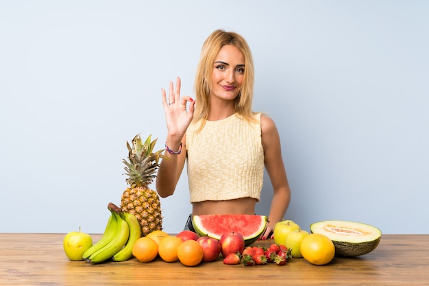 Young blonde woman with lots of fruits showing an ok sign with fingers
