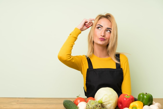 Young blonde woman with lots of vegetables having doubts and with confuse face expression
