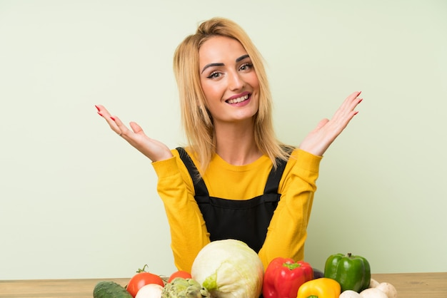 Young blonde woman with lots of vegetables laughing