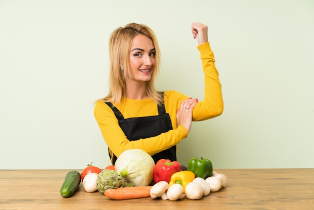 Young blonde woman with lots of vegetables making strong gesture