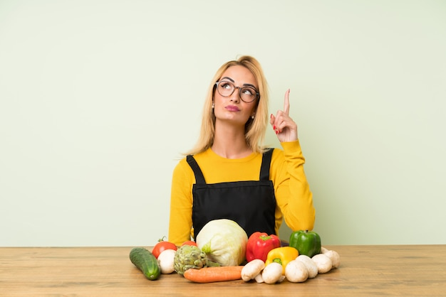 Young blonde woman with lots of vegetables pointing with the index finger a great idea