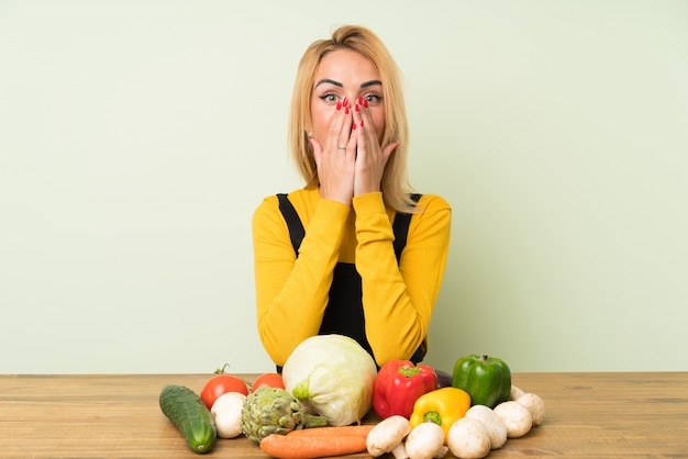 Young blonde woman with lots of vegetables with surprise facial expression