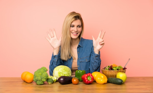 Young blonde woman with many vegetables counting eight with fingers
